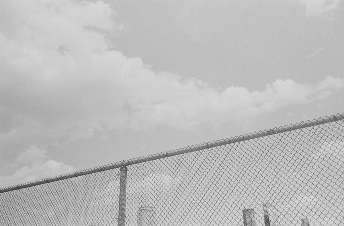 Cloudy sky, wire fence and cityscape skyline